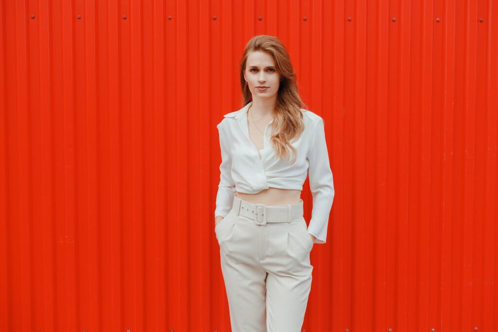 Elegant woman in white top and trousers walking with red metal wall in background
