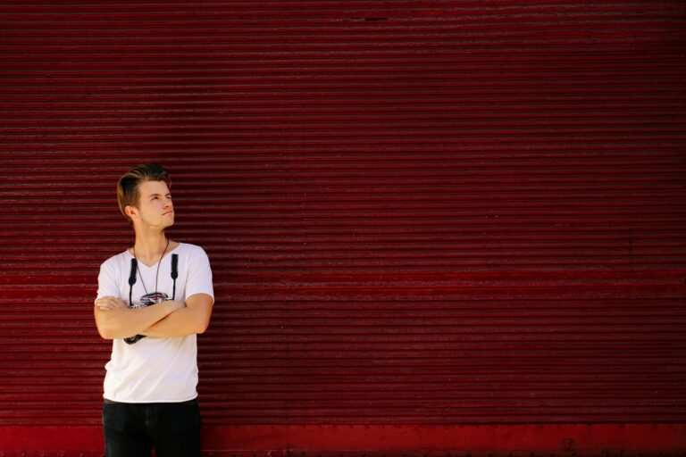 stylish hipster man posing on background of red garage door in sunny street